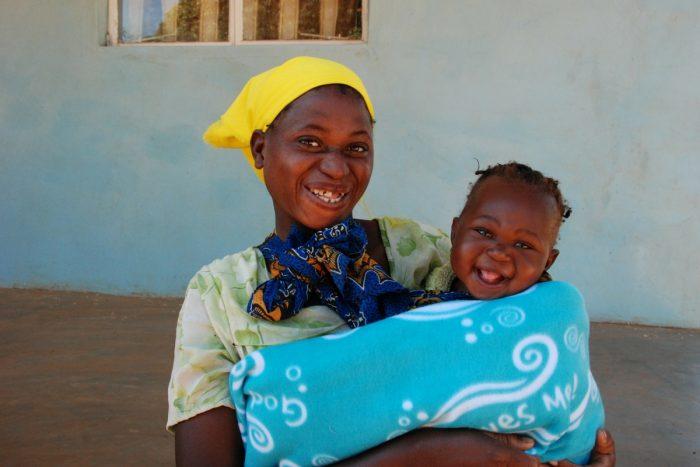 La felicidad en el rostro de esta madre y su hija no tienen precio luego de obtener una cobija con tus donaciones.